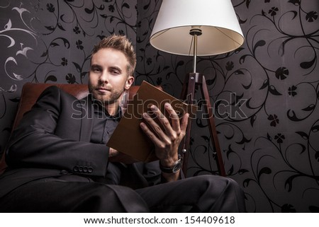 Handsome young man in dark suit with book relaxing on luxury sofa. - stock photo