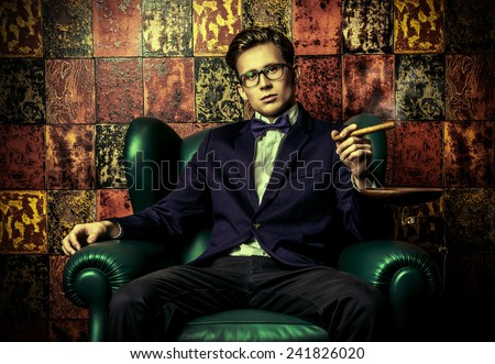Handsome young man in elegant suit smoking a cigar. He is sitting on a leather chair in a luxurious interior.  - stock photo