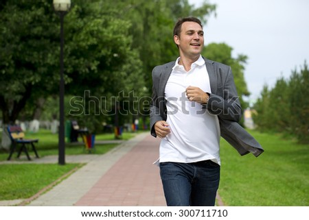Handsome young man in gray suit walking in the summer park  - stock photo
