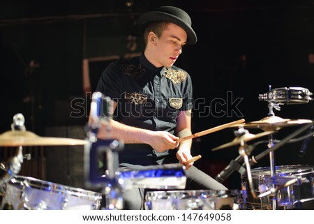 Handsome young man in hat plays drum set in night club. - stock photo
