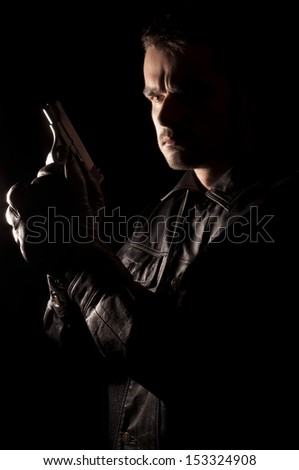 Handsome young man in leather jacket holding a gun - stock photo