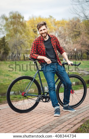 Handsome Young Man In Red Shirt And Blue Jeans Stops Cycling In An Alley With Green Trees Near Lake - stock photo