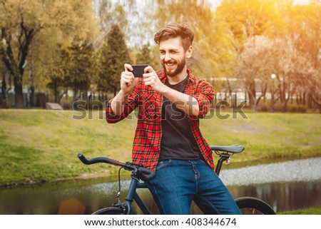 Handsome Young Man In Red Shirt And Blue Jeans Stops Cycling, To Check His Phone In An Alley With Green Trees Near Lake - stock photo