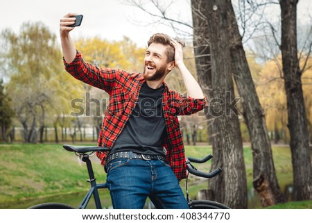 Handsome Young Man In Red Shirt And Blue Jeans Stops Cycling, To Make Selfie On His Phone In An Alley With Green Trees Near Lake - stock photo
