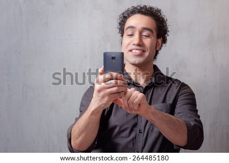 Handsome young man in shirt holding mobile phone and taking photo by phone camera while standing against grey background - stock photo