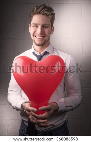 Handsome young man in shirt, tie with valentines heart smiling, valentines day concept. Relationship. - stock photo