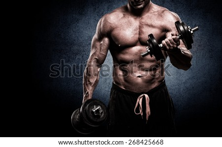 handsome young man in shorts, doing exercises for biceps, on a dark background in the studio - stock photo