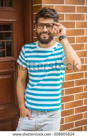 Handsome young man in smart casual wear is posing and looking at the camera.