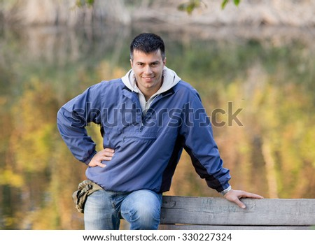 Handsome young man in sport jacket leaning on bench in the park and looking at camera