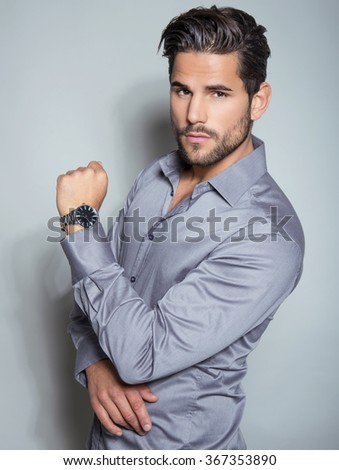 handsome young man in suit on grey background. Business man with wrist watch - stock photo
