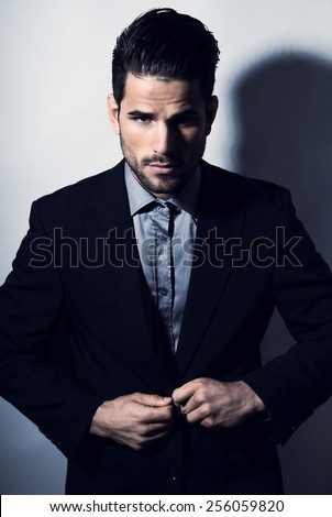 handsome young man in suit posing on grey background - stock photo