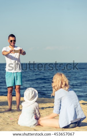 Handsome young man in sun glasses is taking photo of his beautiful wife and little daughter using a smartphone, standing on the sunny beach