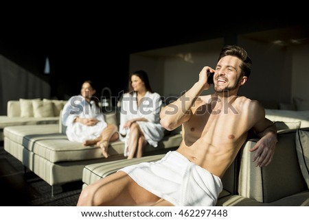Handsome young man in towel using mobile hone in the room with two women