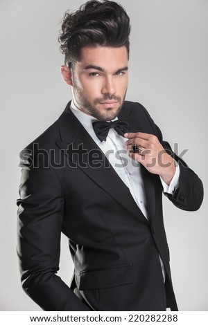 Handsome young man in tuxedo ajusting his bow tie while looking at the camera - stock photo