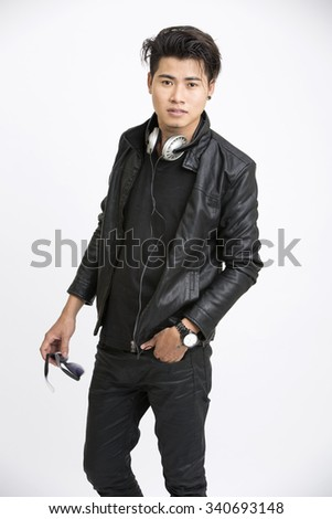 Handsome young man in urban style with headphone on white. - stock photo
