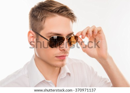 Handsome young man in white shirt adjusting his glasses