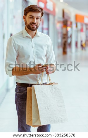 Handsome young man in white shirt holding shopping bags, using a smart phone and smiling while standing in mall - stock photo