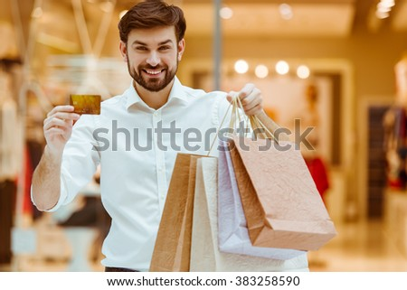 Handsome young man in white shirt smiling, holding shopping bags and a credit card while standing in mall - stock photo