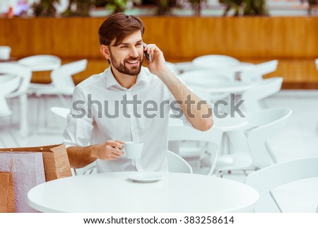 Handsome young man in white shirt talking on a mobile phone, drinking coffee and smiling while resting in cafe after doing shopping - stock photo