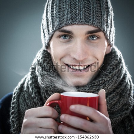 Handsome young man in winter clothes holding a cup of hot tea. - stock photo