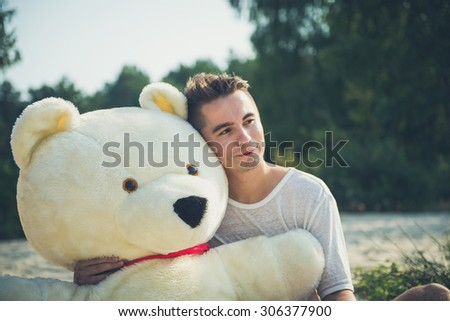 Handsome young man is fooling around with his massive teddy bear. - stock photo