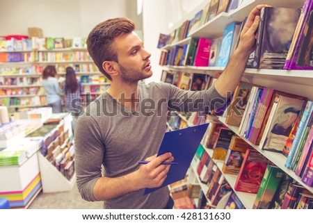 Handsome young man is holding a folder and making notes while choosing a book at the bookshop - stock photo