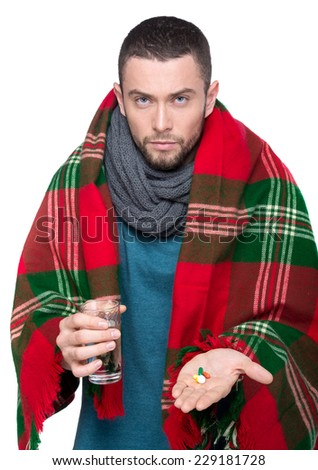 Handsome young man is  holding a pills and glass of water. - stock photo