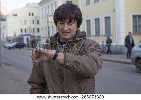 Handsome young man is late. Man checking his wrist-watch - stock photo