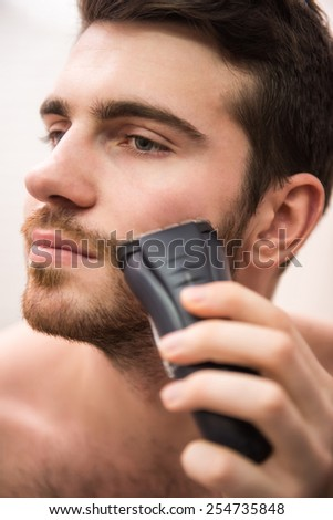 Handsome young man is shaving with electric razor while looking at the mirror. - stock photo