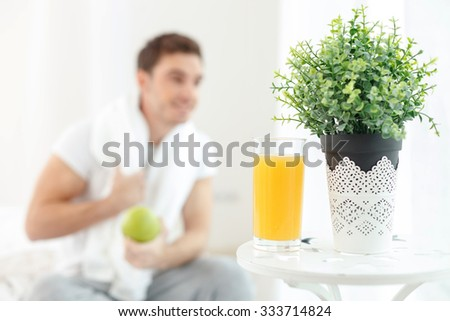 Handsome young man is sitting near the window in bedroom. He is eating an apple and smiling. The man is holding a white towel on his neck. Focus on a glass of orange juice - stock photo