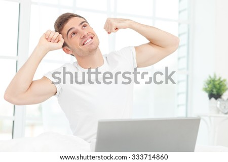 Handsome young man is sitting on bed and stretching his hands up. He is looking up happily and smiling. The man is using a laptop - stock photo