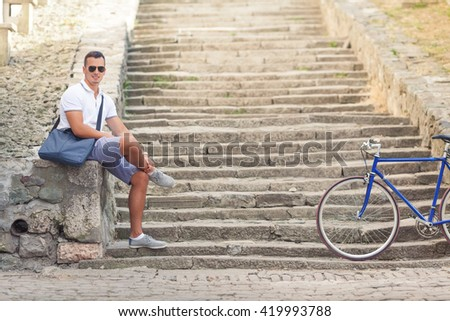 Handsome young man is sitting on the stairs of a fortress while his bicycle is beside him - stock photo