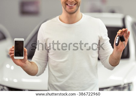 Handsome young man is smiling, holding keys and a smart phone while standing in a motor show, cropped - stock photo