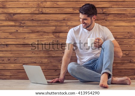 Handsome young man is using a laptop, holding a cup of drink and smiling, sitting on floor against wooden wall - stock photo
