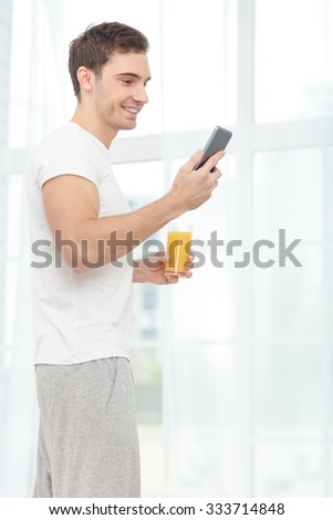 Handsome young man is using a mobile phone. He is standing and drinking juice in his bedroom. The man is smiling - stock photo