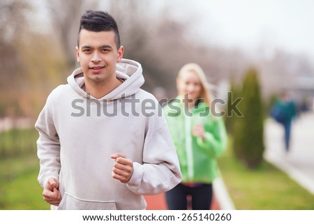 Handsome young man jogging on running track in a park. Unrecognizable woman jogging in the background. - stock photo