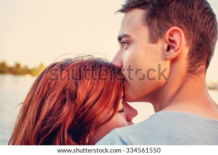 Handsome young man kissing his girlfriend near the river - stock photo