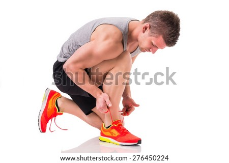 Handsome young man kneeling and tying sneaker, ready to run. Isolated on white - stock photo