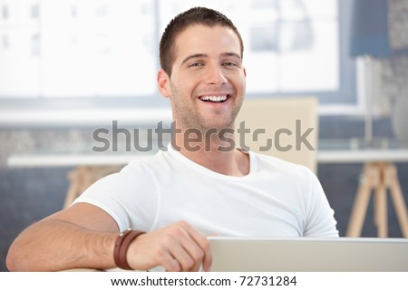 Handsome young man laughing happily at home.? - stock photo