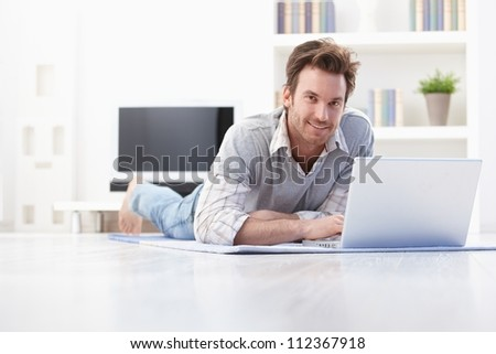 Handsome young man laying on floor at home, browsing internet, smiling. - stock photo