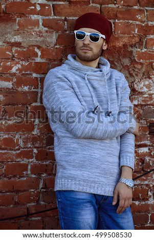 Handsome young man leaning against the brick wall on the street. Men's beauty, fashion.