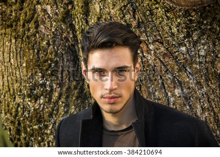 Handsome young man leaning against tree - stock photo