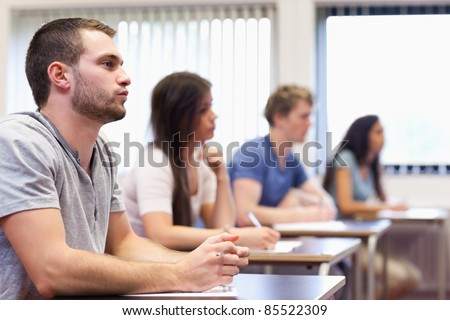 Handsome young man listening in a classroom - stock photo