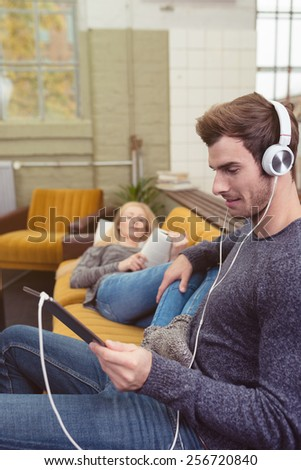 Handsome young man listening to his music on stereo headphones as he relaxes at home on the sofa with his wife checking the tunes on his tablet-pc - stock photo