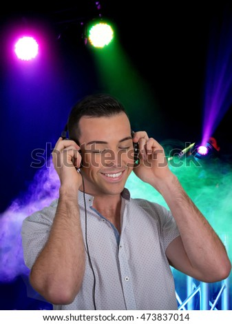 Handsome young man listening to music on earphones with lights and smoke in background