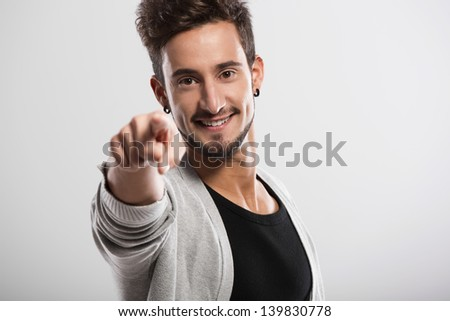 Handsome young man looking and pointing to the camera, over a gray background - stock photo