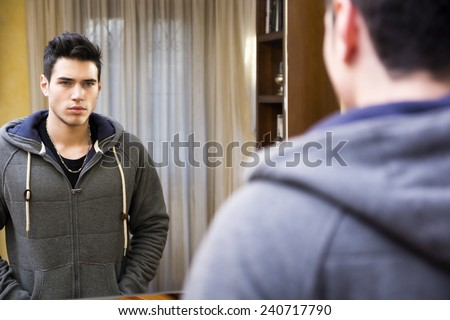Handsome young man looking at his reflection in the mirror in living room at home - stock photo