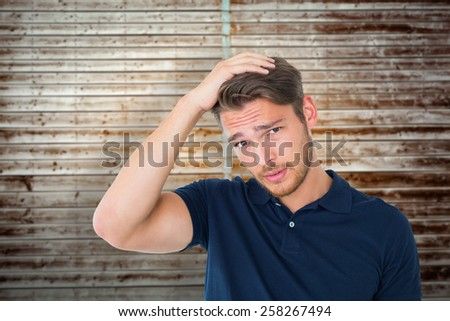 Handsome young man looking confused against wooden planks - stock photo