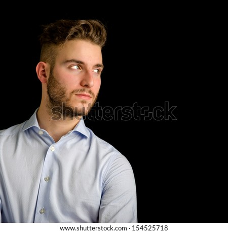 Handsome young man  looking to a side, large copy-space, isolated on black background - stock photo