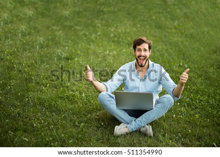 handsome young man lying down in the grass with laptop just gets good news, happy winner